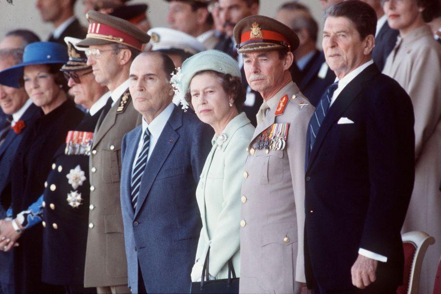 Les reines Beatrix des Pays-Bas et Elizabeth II d'Angleterre, les rois Olav V de Norvège et Baudouin de Belgique, le grand-duc Jean de Luxembourg avec François Mitterrand et Ronald Reagan à Utah-Beach, le 6 juin 1984