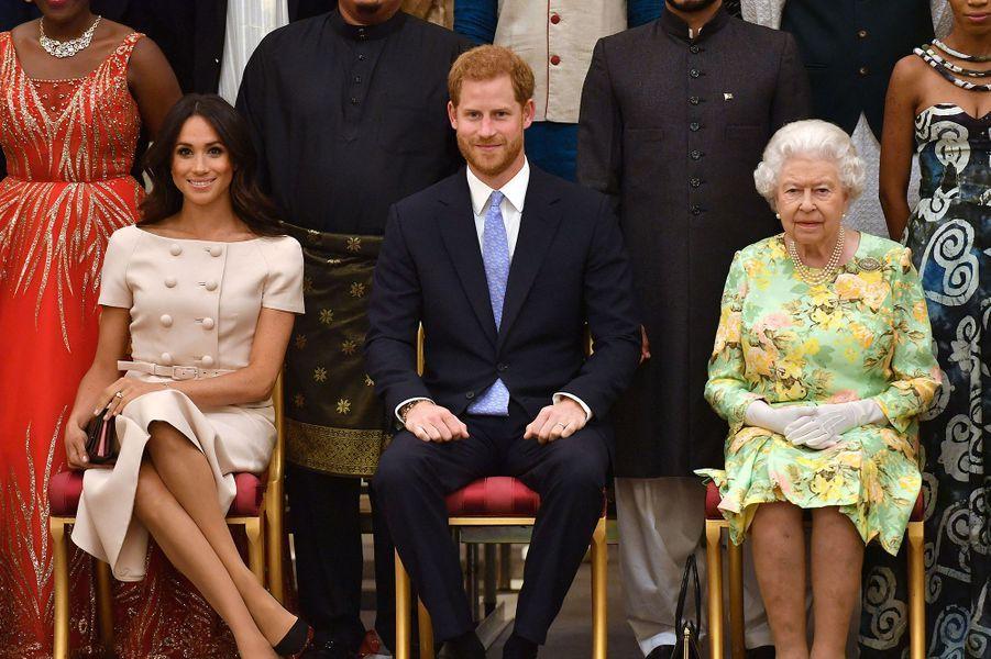 Meghan et Harry au côté de la reine Elizabeth II à la cérémonie Queen's Young Leaders Awards au palais de Buckingham à Londres le 26 juin 2018