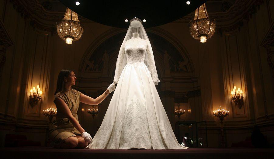 En satin blanc et ivoire, la robe de mariée de la duchesse de Cambridge est pourvue de manches en dentelle, reprenant les emblèmes du Royaume-Uni: la rose, du chardon, la jonquille et le trèfle. Désirant représenter une fleur qui éclot, Sarah Burton a sollicité la maison française Solstiss pour la partie inférieure de sa création.