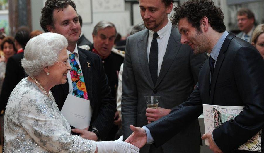 """La reine d'Angleterre a visité mercredi la Royal Academy of Art de Londres. La souveraine a décerné une série de """"Diamond Jubilee Awards"""" aux personnalités ayant contribué au rayonnement de la culture du royaume. Les chanteurs Paul McCartney, Bono, les créatrices Vivienne Westwood, Sarah Burton ou encore les mannequins Agyness Deyn et Lily Cole ont assisté à la soirée de prestige."""