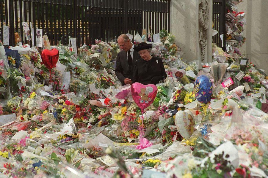 """La reine Elizabeth II dans la """"mer de fleurs"""" deposées devant Buckingham apres la mort de Diana (septembre 1997)"""