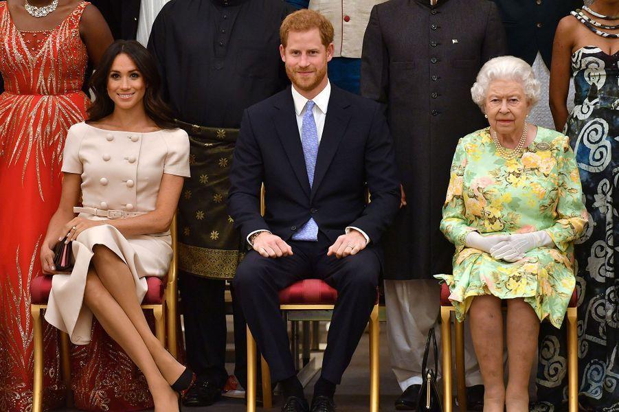 Meghan et Harry au côté de la reine Elizabeth II lors d'une réception à Buckingham Palace le 26 juin 2018