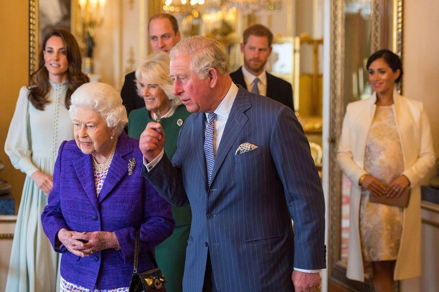 Meghan et Harry (au fond) avec les membres de la famille royale lors du 50e anniversaire de l'investiture du prince Charles à Buckingham le 5 mars 2019