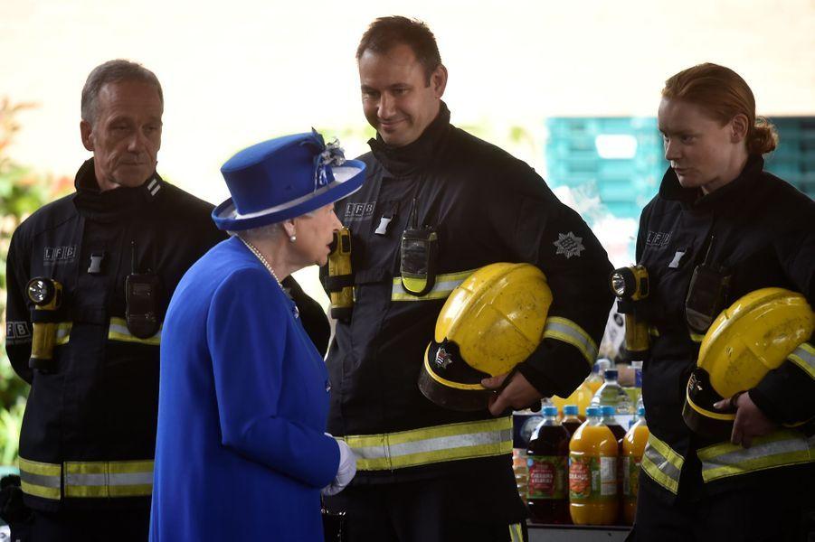 La reine Elizabeth II avec des pompiers au Westway Sports Centre à Londres le 16 juin 2017