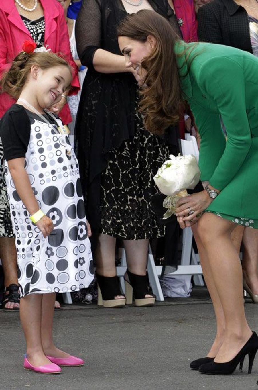 Une petite fille parle avec Kate, après lui avoir remis un bouquet de fleurs à Hamilton, où la duchesse a visité un hospice.