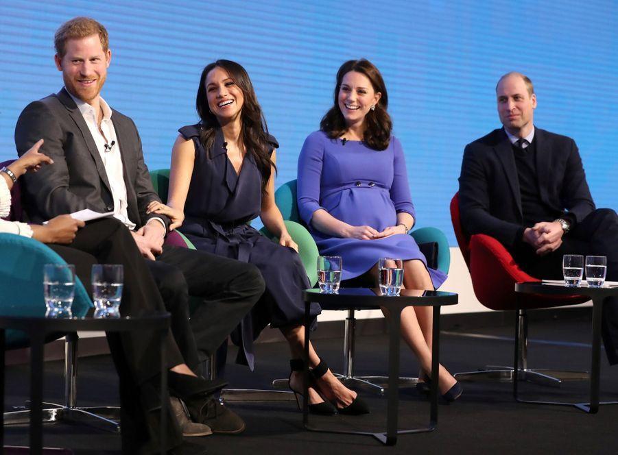 Deux couples, deux styles. Meghan, la main sur le bras d'Harry, en compagnie de Kate et William, les mains croisées, lors du premier forum annuel de leur Royal Foundation, à Londres le mercredi 28 février 2018.