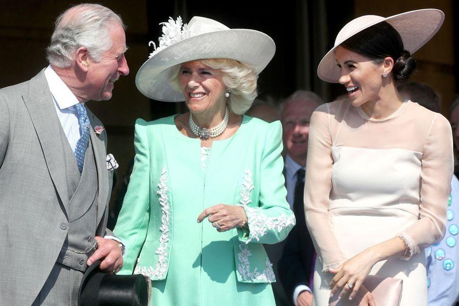 """Le Prince de Galles, Camilla et Meghan """"C'était un moment rare dans les jardins de Buckingham Palace : le Prince de Galles, Camilla la duchesse de Cornouailles et Meghan éclatent de rire alors que le Prince Harry prononce un discours."""""""