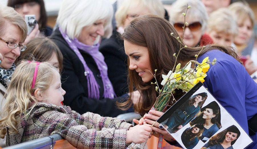Quelques instants auparavant, Kate s'était prêtée, avec sa gentillesse et sa décontraction naturelles, au jeu des bises et des poignées de main. Une petite fille tend un bouquet de fleurs jaunes en agitant un petit drapeau orné de photos de son idole.