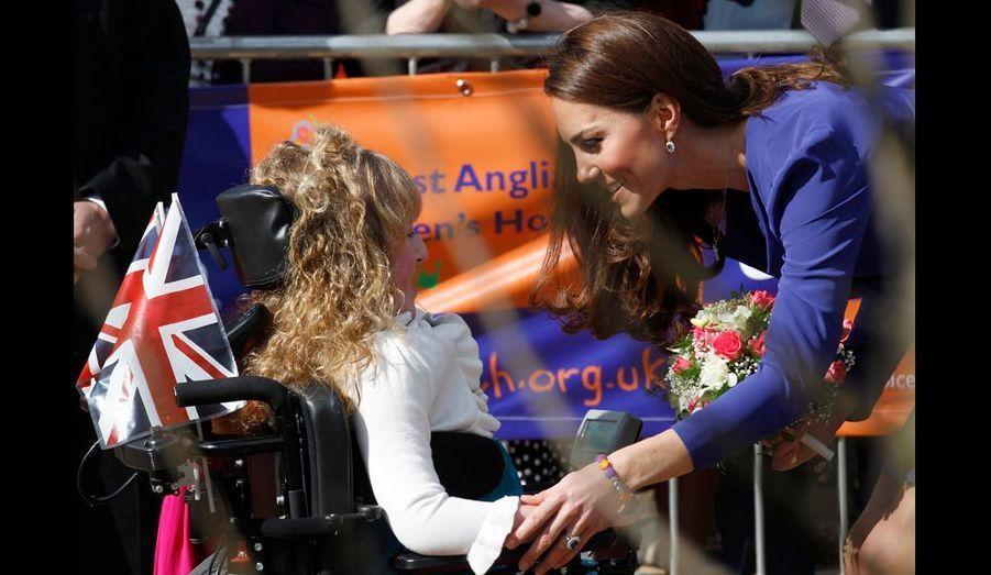 Kate pose tendrement la main sur le bras de cette jeune fille clouée dans une chaise roulante. Elle n'hésite jamais à souligner d'un geste affectueux la gentillesse de son sourire.