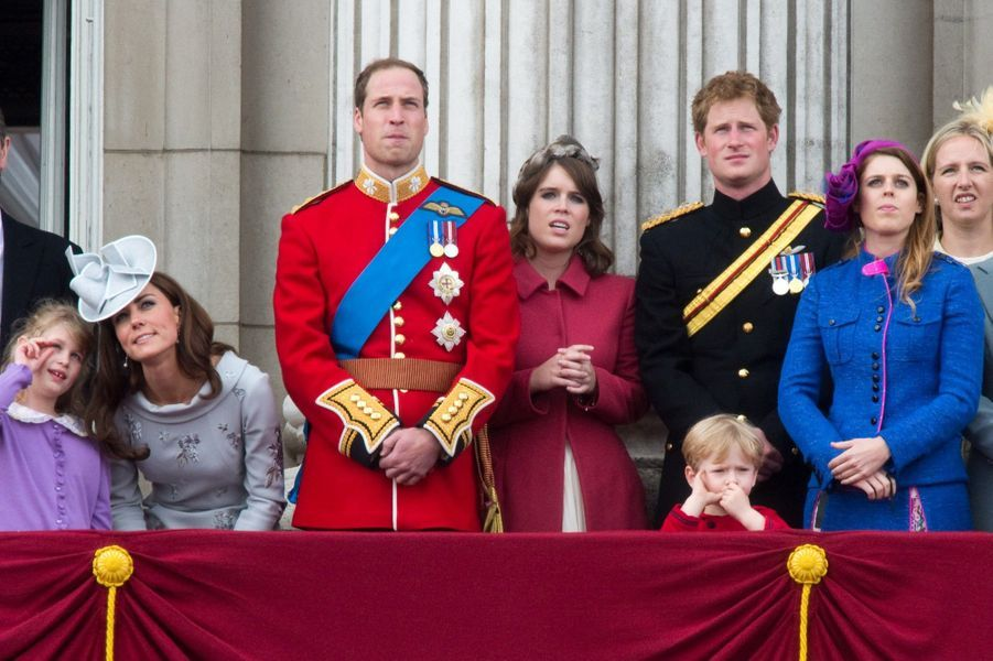 Le prince Harry et la princesse Eugenie concentrés lors d'une cérémonie depuis le balcon du palais de Buckingham à Londres en 2012.