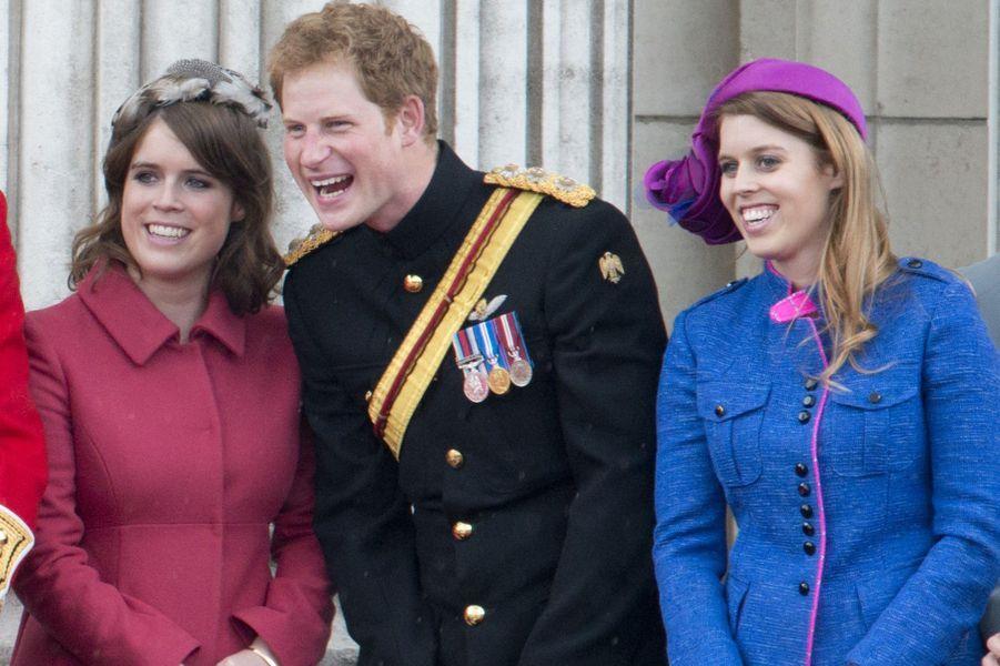 Le prince Harry plaisante avec la princesse Eugenie à sa droite, la princesse Beatrice se trouve à sa gauche.