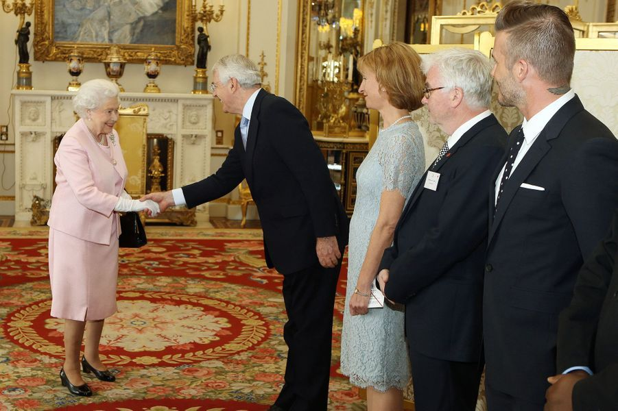 La reine Elizabeth II salue son ancien Premier ministre John Major à Buckingham Palace, le 22 juin 2015