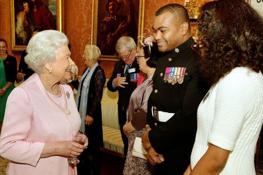 La reine d'Angleterre Elizabeth II reçoit avec le prince Philip des héros détenteurs de la Victoria Cross et de la George Cross au palais de Bu...