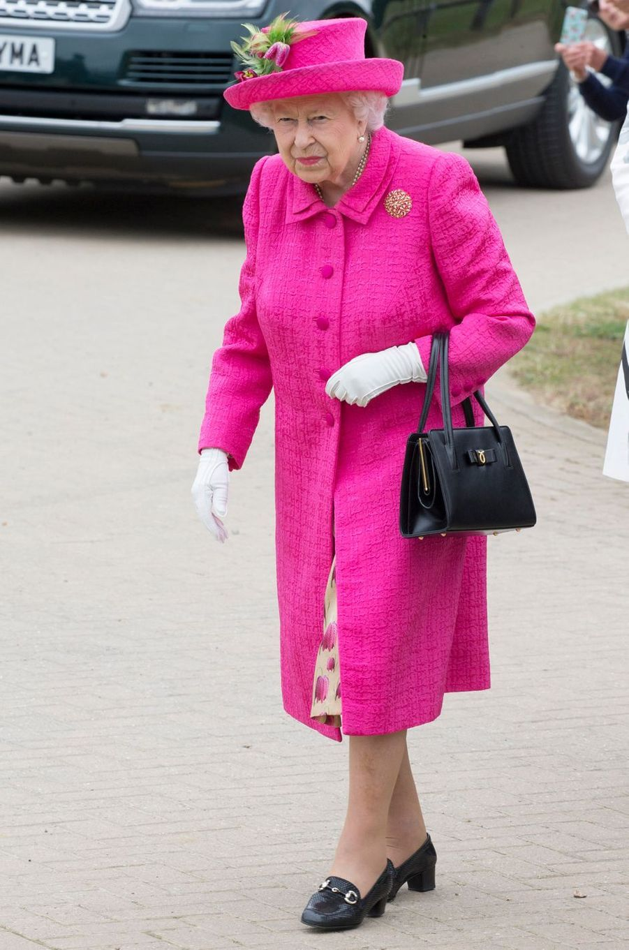 La reine Elizabeth II en rose flashy à Cambridge, le 9 juillet 2019