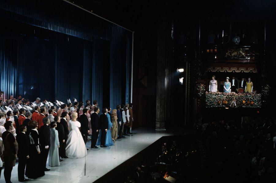 """La reine Elizabeth II regarde la scène du London Palladium, où la chanteuse Mireille Mathieu en robe bleue, chante le """"God Save the Queen"""", le 16..."""