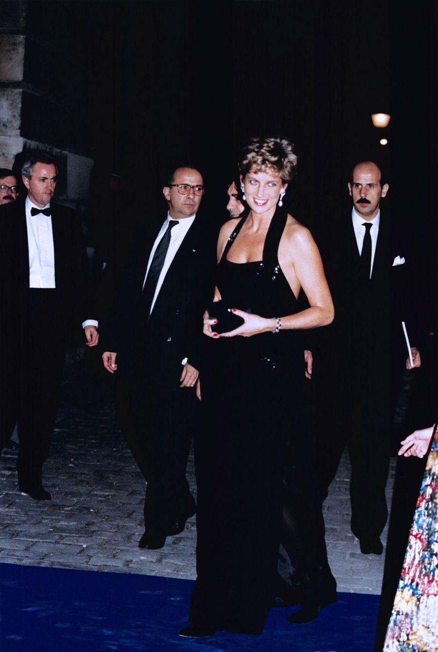 « Diana, à son arrivée au château, porte une robe de crêpe noir de Bruce Oldfield, qui est l'un de ses couturiers favoris. Avec son décolleté plongeant, la robe est bordée de paillettes, et une longue fente laisse entrevoir les jambes de la princesse. » - Paris Match n°2376, 8 décembre 1994