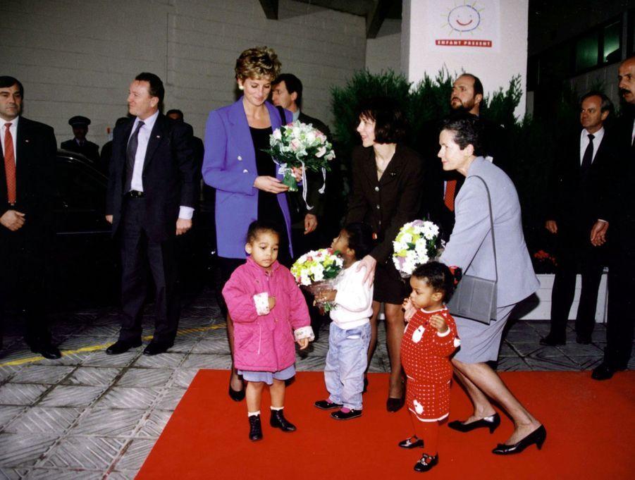 La princesse Diana en compagnie d'Anne-Aymone Giscard d'Estaing, lors d'une visite dans une crèche accueillant les enfants de parents en difficulté, dans le XXe arrondissement de Paris, le 28 novembre 1994.