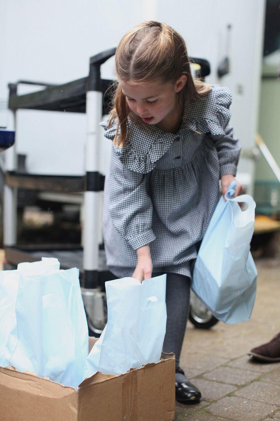 La princesse Charlotte distribue des paniers alimentaires pendant la pandémie, devant l'objectif de sa mère, Kate Middleton.
