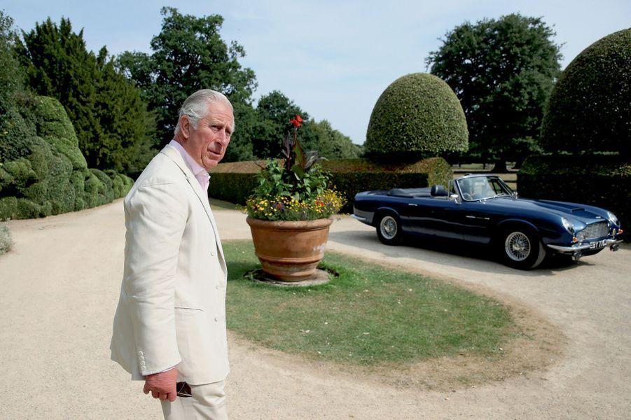 Devant l'Aston Martin qu'il conduit depuis ses 21 ans. Il a fait transformer le moteur pour qu'il carbure au… surplus de vin blanc.