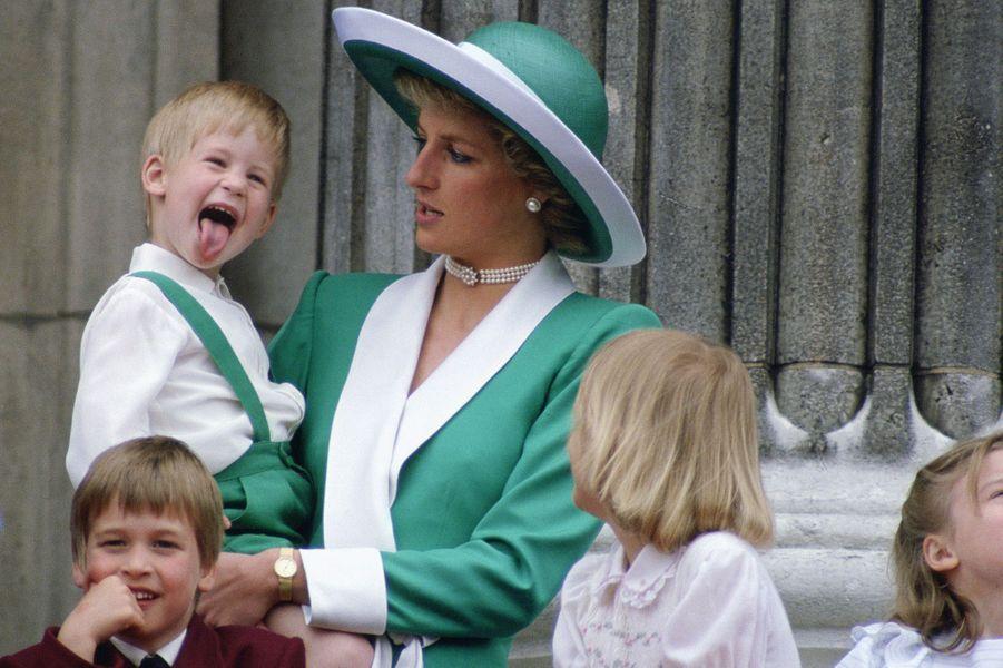 Le prince Harry tirant la langue dans les bras de Diana lors de la parade Trooping The Colour au palais de Buckingham en juin 1988