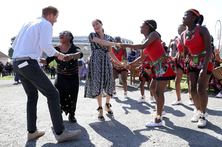 Meghan et Harrydansent lors d'une visite dans la banlieue de Nyanga au côté de l'initiative Justice Desk au Cap, le 23 septembre 2019