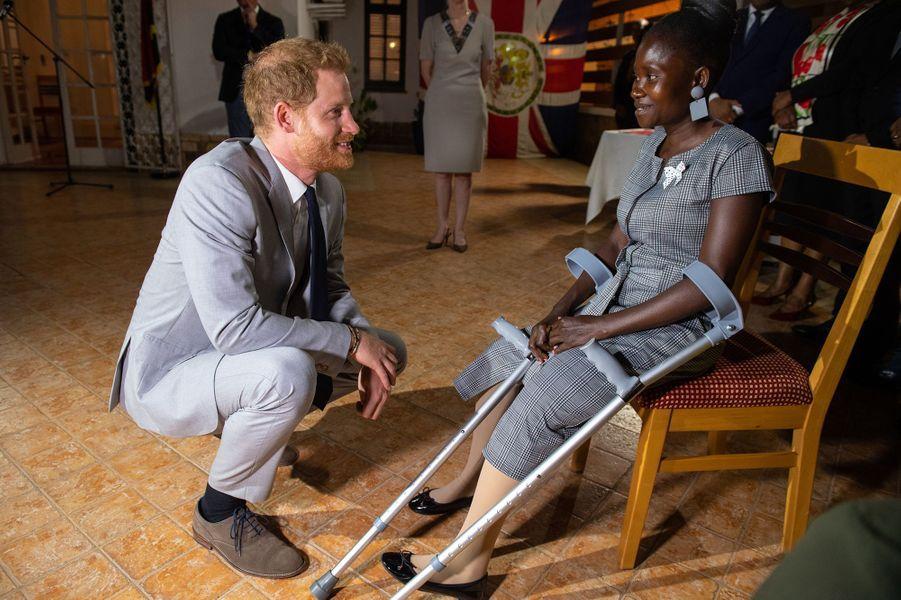 Le prince Harry passe un moment avec Sandra Tigica, une jeune femme victime des mines antipersonnel qui avait rencontré la princesse Diana lors de sa visite en Angola en 1997, le 27 septembre 2019 à Luanda