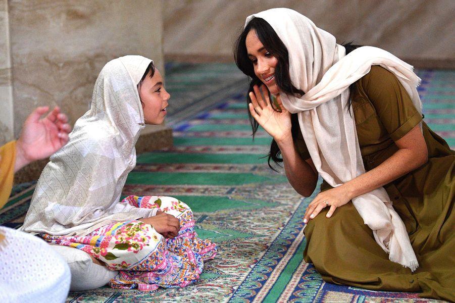 Meghan discute avec une fillette lors de sa visite à la mosquée Auwal lors de la fête du patrimoine au Cap, le 24 septembre 2019