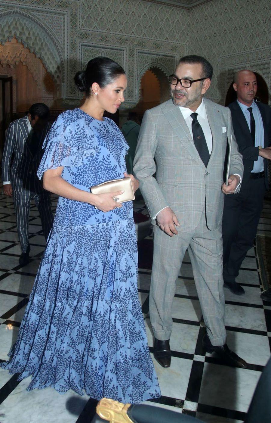 Précédé par Meghan, resplendissante dans sa longue robe bleue à motif fleuri, le prince Harry, en costume clair, aprésenté des lettres de la reine Elizabeth II au souverain.