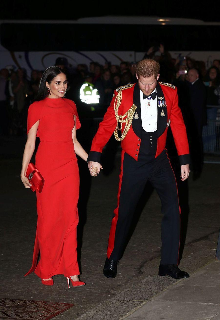 Meghan Markle, dans une robe rouge grifféeSafiyaa, et le prince Harry arriventMountbatten Festival of Music au Royal Albert Hall à Londres le 7 mars 2020.