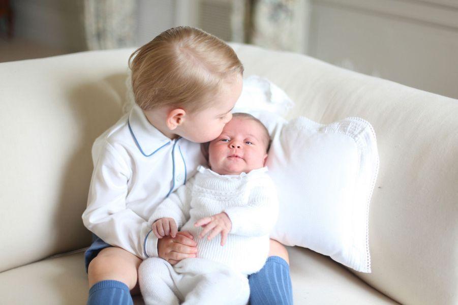 Le prince George tient dans ses bras la princesse Charlotte.