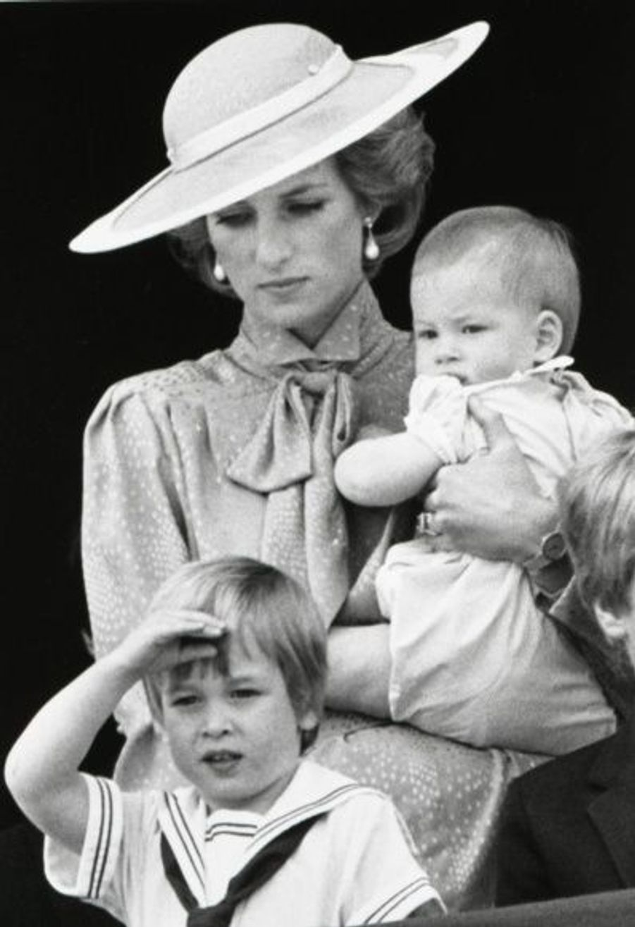 Alors que son frère Harry est dans les bras de sa mère Diana pour sa première apparition, William salue les troupes depuis le balcon de Buckingham Palace, le 15 juin 1985.