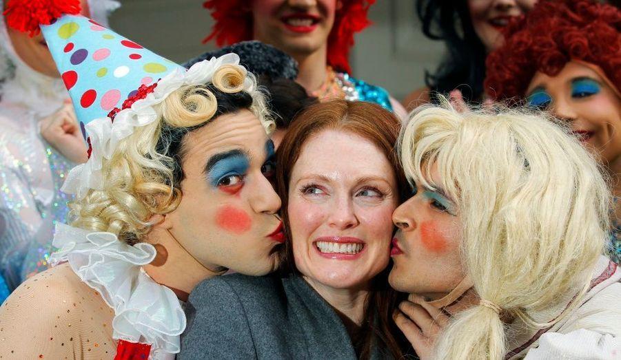 Julianne Moore reçoit un baiser de Brandon Ortiz (à gauche) et d'Aseem Shukla, deux membres de la troupe Hasty Pudding Theatricals, à l'université d'Harvard. L'actrice a été nommée Femme de l'année par la compagnie théâtrale réputée pour ses comédies musicales burlesques.