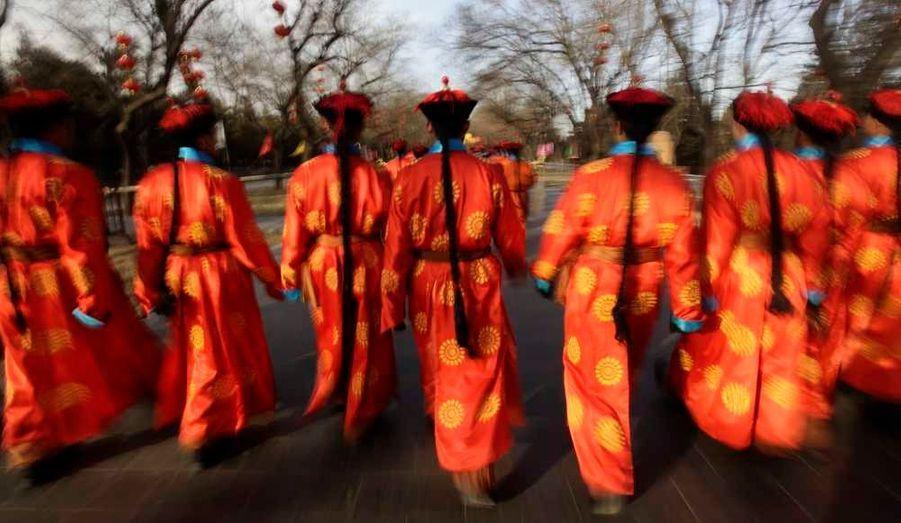 Des Chinois habillés en costumes de la Dynastie Qing pour une cérémonie de culte à Pékin.