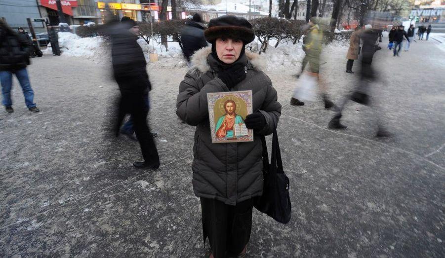 Une femme tient dans ses mains une icône religieuse en hommage aux victimes de l'attentat terroriste qui a touché l'aéroport moscovite de Domodedovo.