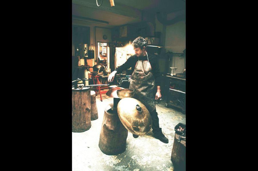 Nathanaël le Berre Dinandier, de métal en magie Il y a de la chair et du son dans ses créations. Ni fondeur ni forgeron, le dinandier à l'origine fabrique des contenants à partir de feuilles de métal. Ils sont trois ou quatre en France à exercer cette poésie frappée qui devient vase, table, lampe, mais qui est avant tout sculpture. Etudiant à l'école Olivier de Serres, Nathanaël, ci-dessus, dans son atelier d'Aubervilliers,découvre ce métier rare et oublié enseigné dans les années 1950 par Serge Mouille, dont les luminaires s'arrachent aujourd'hui à prix d'or. Peu à peu, le jeune Bourguignon, élevé dans une famille d'artistes, donne vie à ses outils. En 2014, il est lauréat du prestigieux prix Liliane Bettencourt pour l'intelligence de la main. Cette année, le décorateur Tristan Auer lui a proposé de créer une pièce pour l'hôtel de Crillon, place de la Concorde. Il est aussi l'invité officiel du Japon avec quinze autres artisans français d'exception en septembre, vénérés au pays du Soleil-Levant comme des objets précieux : on les qualifie de trésor national vivant. nathanael-leberre.fr