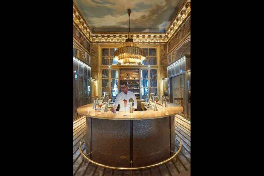 Julien, l'un des barmen, prend ses marques derrière le spectaculaire comptoir taillé dans une pierre mordorée dite «brown stalatite». L'une des cinquante-trois variétés de marbres utilisés dans la restauration de l'édifice.