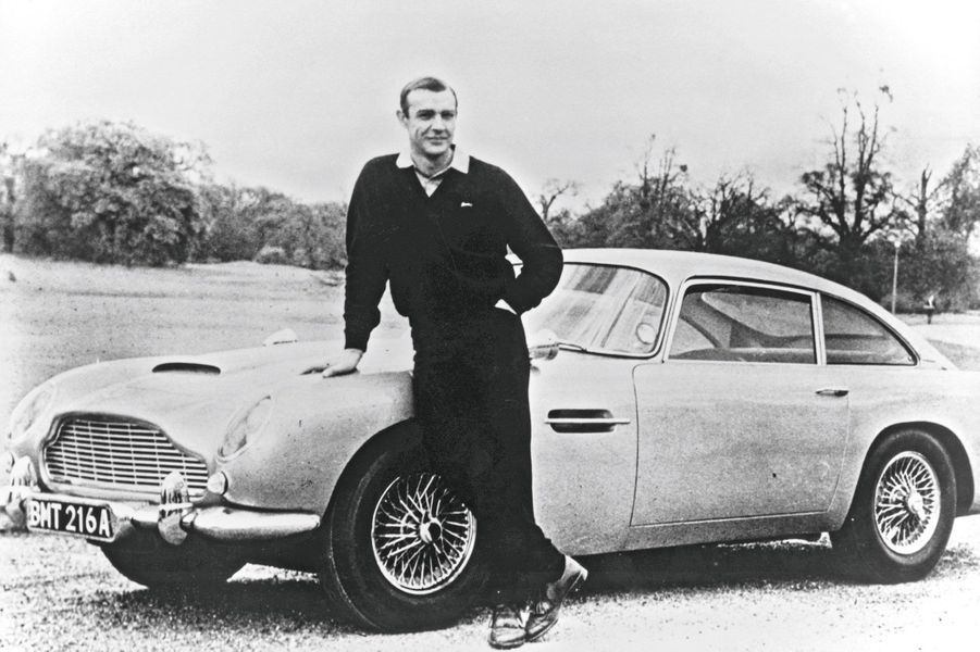 Depuis cent ans, la marque automobile préférée des femmes fait rêver les hommes. Symbole de puissance, de raffinement et d'élégance, Aston Martin vit au rythme de James Bond, son héros préféré, avec ses spectaculaires coups d'éclat, ses faillites retentissantes et ses stupéfiantes résurrections. De Sean Connery (« Goldfinger », 1964) à Daniel Craig (« Skyfall », 2012) en passant par Pierce Brosnan (« GoldenEye », 1995, et « Demain ne meurt jamais », 1997), la DB5 a toujours eu la préférence de James Bond. Fabriquée à un peu plus d'un millier d'exemplaires, l'anglaise arbore une silhouette de star et un « six en ligne » de 242 chevaux. Sa cote varie, aujourd'hui, entre 70 000 € et 270 000 €. Par Lionel Robert