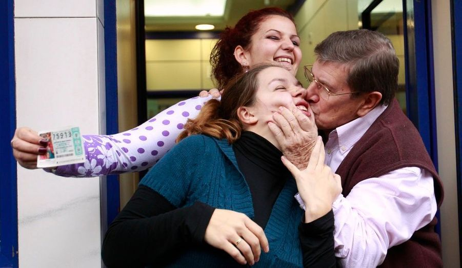 """Juan Angel Gonzalez, propriétaire de l'une des boutiques de loterie qui a vendu le troisième prix de """"El Gordo"""", embrasse sa fille Maria dans leur boutique de loterie à Madrid. Le jackpot, de 2,3 milliards d'euros, a été divisé parmi des centaines de numéros gagnants."""