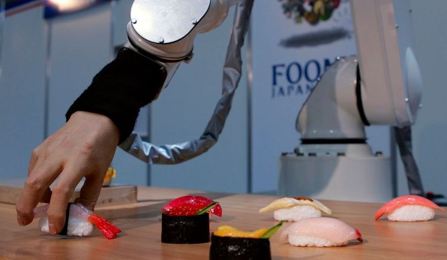 Un robot munis de doigts en plastique confectionne des sushis, lors de l'exposition Japonaise sur les machines technologiques et la cuisine.