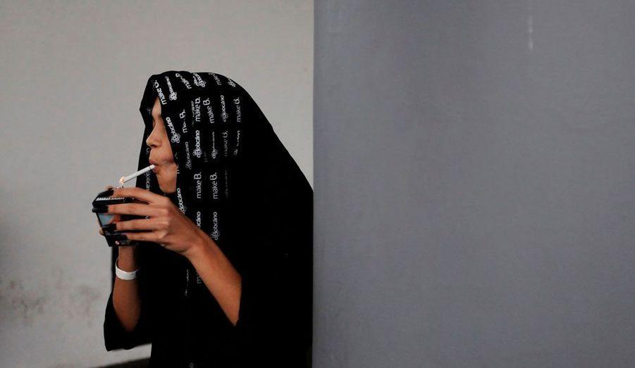 Un mannequin profite d'un instant de répit pour s'allumer une cigarette lors de la Fashion Week Automne-Hiver 2012 de Sao Paul au Brésil.