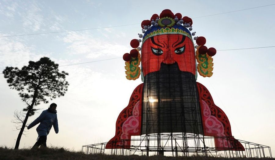 Une femme passe devant une lanterne représentant un des interprètes vedettes de l'opéra chinois au cours des travaux d'installations du premier festival de lanternes organisé à Heifei, dans la province de l'Anhui. Le coup d'envoi de l'événement, qui comptera plus de 100 lanternes, sera donné le 18 décembre.
