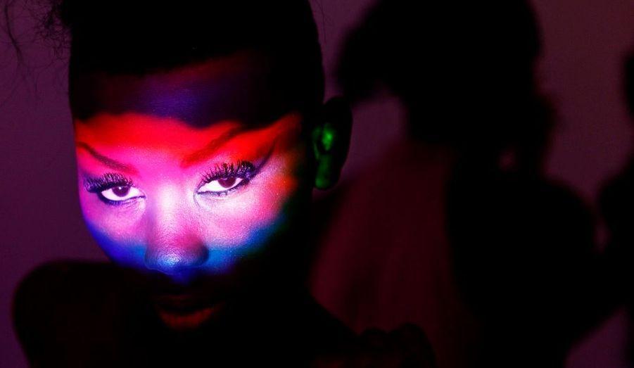 Des reflets colorés illuminent le visage de tigresse du mannequin Sira Sissoko, tandis qu'elle patiente dans les coulisses de la Fashion Week de Dakar au Sénégal.