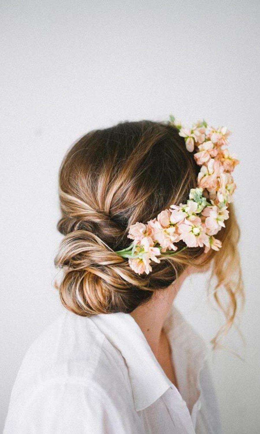 Un chignon flou romantique avec des fleurshttps://www.pinterest.fr/pin/354095589432916294/