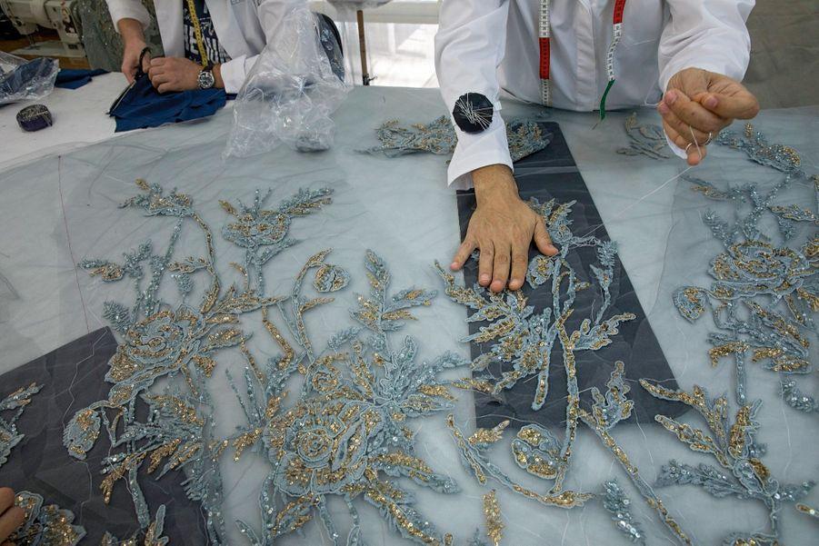 Broderies et sequins sur fond de tulle bleu pâle, la marque de fabrique du couturier. Détail d'une robe de la collection haute couture automne-hiver 2017-2018