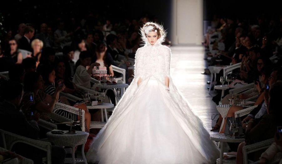 """Comme à son habitude à l'occasion de la Fashion Week de Paris, la maison Chanel a organisé son défilé Haute Couture au Grand Palais. Pour sa collection automne-hiver baptisée """"new vintage"""", Karl Lagerfeld a voulu remettre au gout du jour les pièces mythiques créées par Coco Chanel. Les mannequins ont ainsi notamment défilé avec les fameux tailleurs en tweed, recolorés cette saison en rose et en gris, et de longues robes brillantes et décolletées."""