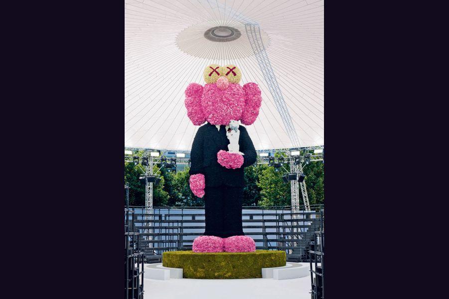 Kaws pour Dior Homme Issu de la scène new-yorkaise du graffiti, Kaws et ses figurines aux accents pop art étaient les invités du premier défilé de Kim Jones chez Dior Homme, en juin 2018. Ce street artiste est connu pour son personnage Companion, croisement entre Mickey, les Simpson et une tête de mort, imaginé en 1999. Il a fait l'objet d'installations monumentales au Rijksmuseum, à Amsterdam ou, récemment, dans la baie de Hongkong. Pour la maison de l'avenue Montaigne, il a créé le désormais célèbre personnage BFF. C'est cette sculpture tout en fleurs format XXL qui a accueilli le public lors de son défilé, avant de devenir une des stars de la nouvelle campagne Dior Homme. Il a aussi redessiné un des symboles chers à M. Dior, l'abeille. Il en donne une version « cartoonesque », essaimée dans un nouveau vestiaire de classiques. Une autre manière de s'initier au street art avec des accessoires en série limitée. dior.com.