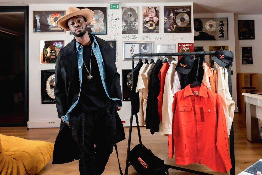 Le 10 décembre, dans les bureaux de sa maison de production. Manteau Ami Paris, veste en jean Loewe, T-shirt Username, jogging Fear of God, sautoir Messika : Dadju maîtrise l'art et le style de mixer des pièces de créateurs à des essentiels du vestiaire streetwear.