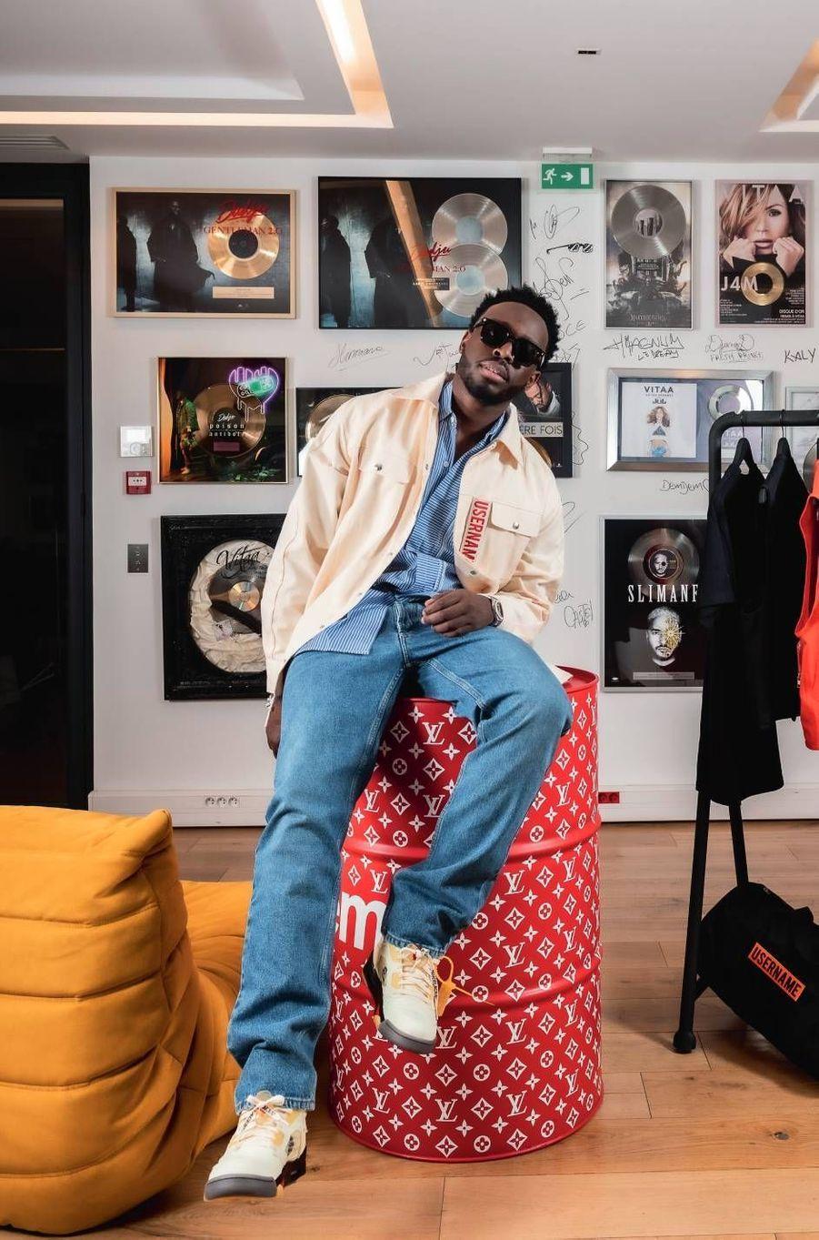 Le chanteur trône fièrement avec la veste et la chemise de sa collection sur le baril issu de la célèbre collaboration entre le label street Supreme et Louis Vuitton.