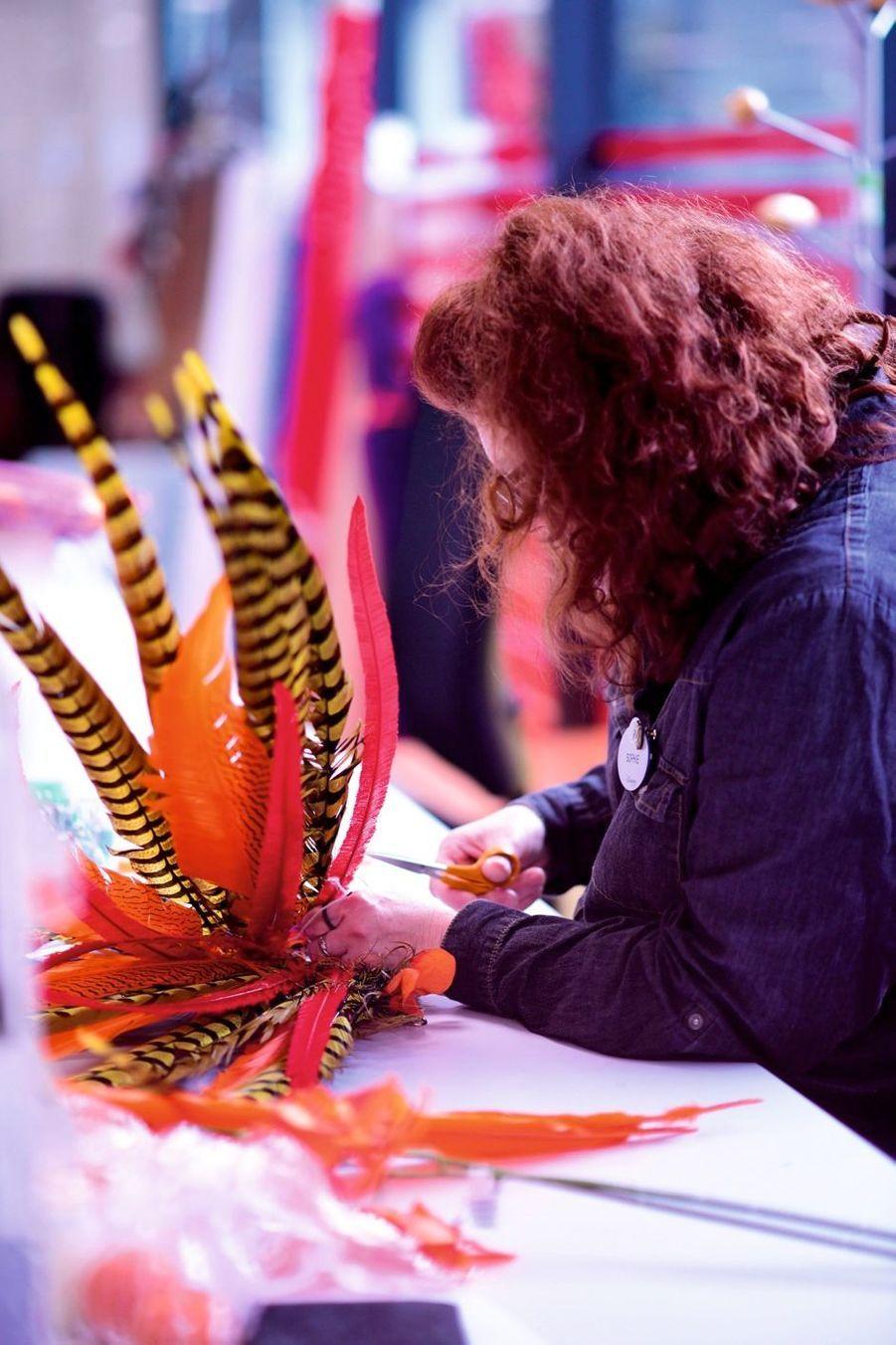 Ci-contre, Sophie Manevy, modiste, réalise une coiffe en plumes piquées à la main une à une.