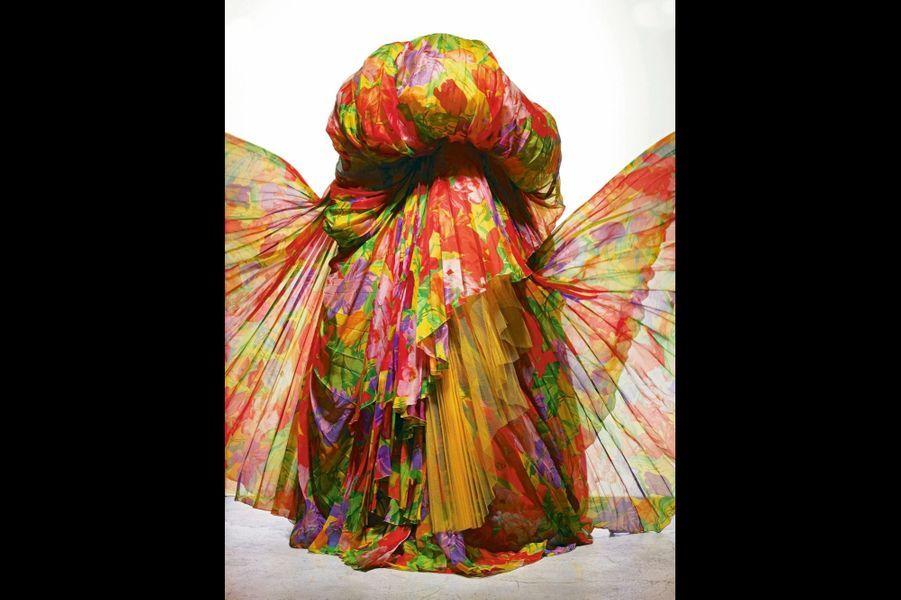 Gianfranco Ferré : L'art du drapé Quand Gianfranco Ferré arrive chez Dior en 1989, la tendance est au postmodernisme. On se penche sur le passé sans avoir peur de le citer. Mais qu'est-ce qui différencie la haute couture du prêt-à-porter ? L'art du détail. Il faut encourager le travail des fournisseurs : brodeurs, plumassiers… Gianfranco Ferré revient au fameux new-look avec les grandes jupes corolles soutenues par des jupons de tulle. Il y ajoute son sens du baroque italien, très théâtral. Le tissu virevolte autour du corps et s'attache à des points très précis, comme s'il était posé par coups de vent. «Eden », collection haute couture printemps-été 1992, Christian Dior par Gianfranco Ferré.